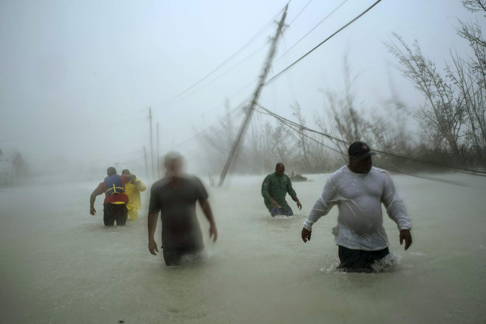 This image released by World Press Photo, Thursday April 16, 2020, by Ramon Espinosa, The Associated Press, which won third prize in the Spot News Singles category, Volunteers wade along a flooded road in Freeport, Grand Bahama, on 3 September 2019, after Hurricane Dorian hit the island. (Ramon Espinosa, The Associated Press, World Press Photo via AP)