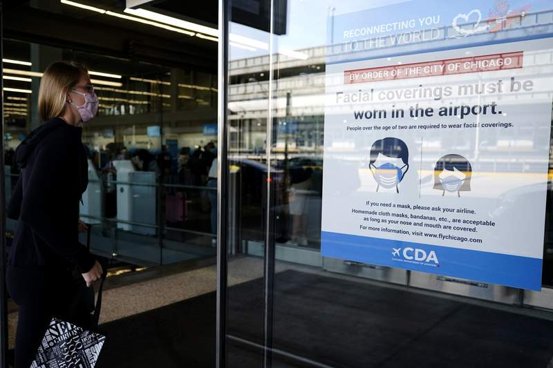 In this July 2, 2021 photo, a traveler walks in Terminal 3 as a sign stating face coverings are required is displayed at O'Hare International Airport in Chicago.  The leading U.S. airlines say that the rise in COVID-19 cases is hurting ticket sales and pushing back the recovery of the travel industry. American, United, Delta, Southwest and others reported setbacks in regulatory filings Thursday, Sept. 9.   (AP Photo/Nam Y. Huh)