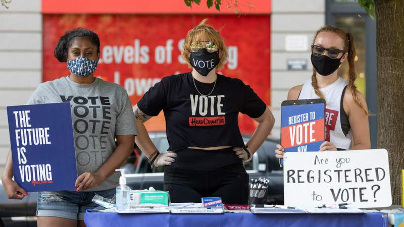 Women wearing masks pose behind a voter registration table in Union Square as the city continues Phase 4 of re-opening following restrictions imposed to slow the spread of coronavirus on August 09, 2020 in New York City. Photo by Alexi Rosenfeld