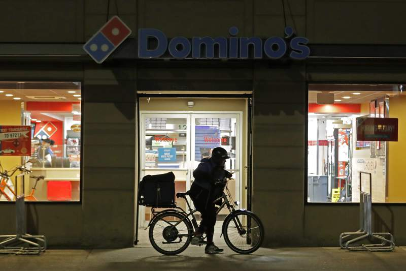 FILE - A delivery worker leaves a Domino's Pizza restaurant in downtown Seattle on a bike, Sunday, March 15, 2020. Dominos Pizza says shortages of cooks, drivers and other staff are pinching sales at its U.S. stores. The worlds largest pizza chain said Thursday, Oct. 14, 2021 its same-store sales __ or sales at stores open at least a year __ dropped 1.9% in the July-September period. It was the first time in a decade that the companys U.S. same-store sales have fallen. (AP Photo/Ted S. Warren, file)
