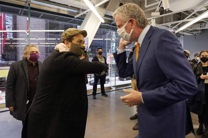Actor Lin-Manuel Miranda, center, and New York Mayor Bill de Blasio, bump elbows before they tour the grand opening of a Broadway COVID-19 vaccination site intended to jump-start the city's entertainment industry, in New York, Monday, April 12, 2021. At left is Miranda's father. Luis A. Miranda, Jr. (AP Photo/Richard Drew, Pool)