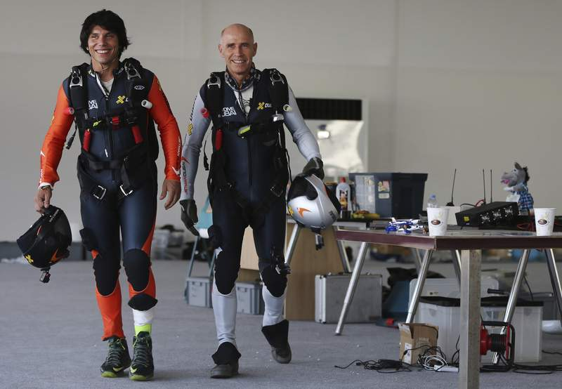 """FILE - In this May 12, 2015, file photo, former Swiss pilot Yves Rossy, known as a """"jetman,"""" right, and his protege Vincent Reffet, prepare for a fly in Dubai, United Arab Emirates. Reffet, one of Dubai's famed """"jetman"""" killed in a crash in November, failed to deploy the emergency parachute attached to the winged engines strapped to his back, an investigative report released Thursday, April 15, 2021 found. (AP Photo/Kamran Jebreili, File)"""