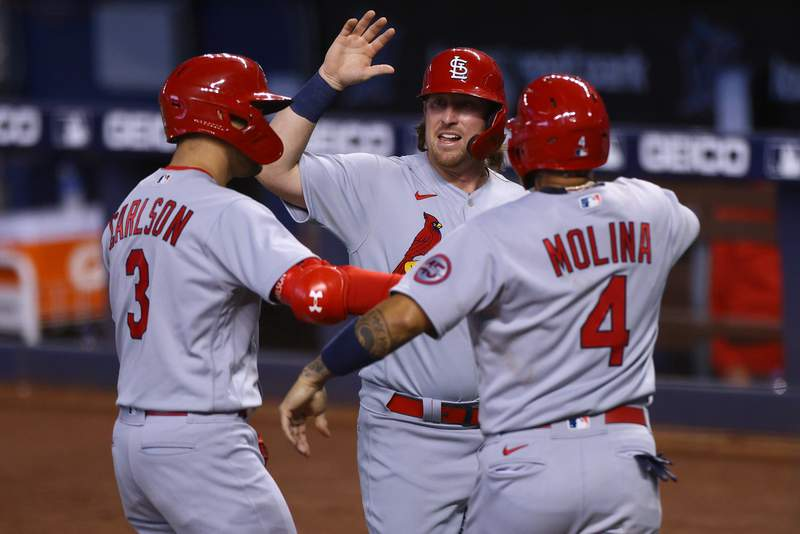 Dylan Carlson, Yadier Molina, and John Nogowski of the St. Louis Cardinals celebrate at homeplate in the ninth inning against the Miami Marlins at loanDepot park on April 07, 2021 in Miami, Florida.