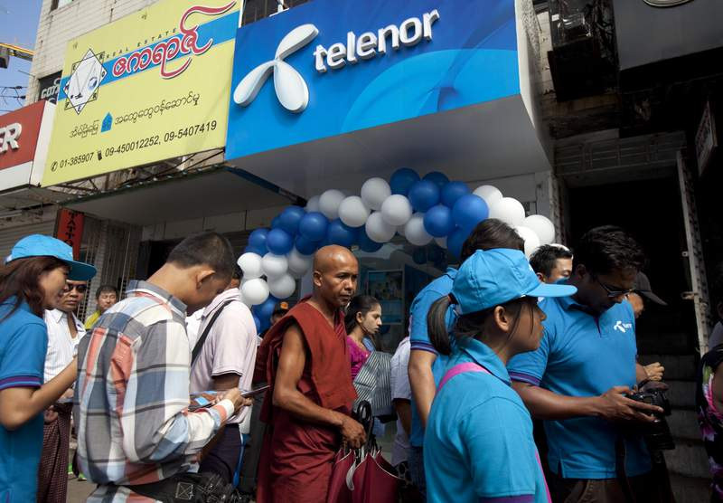 FILE - In this Oct. 26, 2014, file photo, customers including Buddhist monk line up outside a showroom to buy SIM card at Telenor, Norwegian telecommunication company, in Yangon, Myanmar. The Norwegian telecoms company Telenor, one of the biggest carriers in Myanmar, said Thursday, July 8, 2021, it has agreed to sell its entire operations in the country to the M1 Group, a Lebanese-based investment firm, for $105 million.(AP Photo/Khin Maung Win, File)