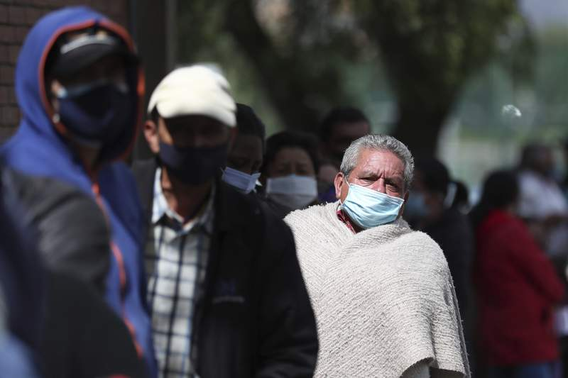 Men line up outside a gym to get a COVID-19 vaccine in Bogota, Colombia, Friday, June 4, 2021.  (AP Photo/Fernando Vergara)