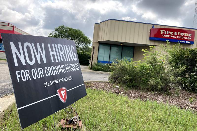 A hiring sign is displayed at Firestone Complete Auto Care store in Arlington Heights, Ill., Wednesday, June 30, 2021. Illinois Governor J.B. Pritzker said that the state may join the list of others that may consider offering incentives for people to return to work.(AP Photo/Nam Y. Huh)