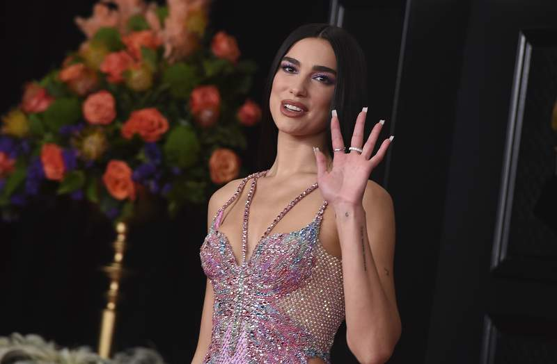 FILE - In this Sunday, March 14, 2021 file photo, Dua Lipa arrives at the 63rd annual Grammy Awards at the Los Angeles Convention Center. British music's leading prize night next month will feature an audience of 4,000 people, in what will be the first major indoor music event in the country to welcome back a live audience since the coronavirus pandemic erupted more than a year ago. This has been a long tough year for everyone and Im delighted the night will honor the key worker heroes who have cared for us so well during that time and continue to do so, said singer/songwriter Dua Lipa, who is set to perform at the event. (Photo by Jordan Strauss/Invision/AP, File)