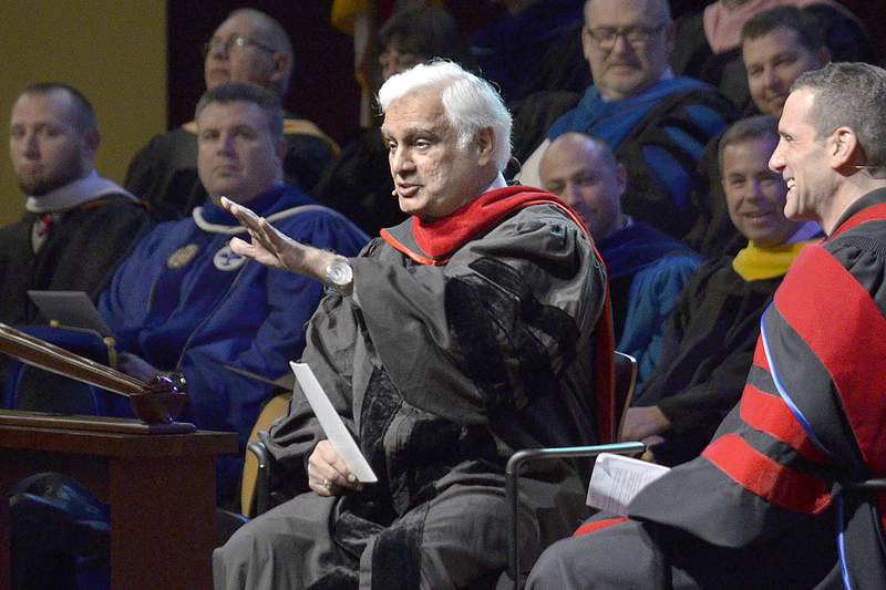 FILE - In this March 30, 2016 file photo, Christian apologist and author Ravi Zacharias, left, talks with associate professor Lenny Luchetti during the Society of World Changers induction ceremony at Indiana Wesleyan University in Marion, Ind.  Zacharias, who built an international ministry that strives to defend Christianity on intellectual grounds, has died in Georgia.   Zacharias died Tuesday, May 19, 2020 at his home in Atlanta after a brief battle with sarcoma, Ravi Zacharias International Ministries said in a statement. (Jeff Morehead/The Chronicle-Tribune via AP, File)