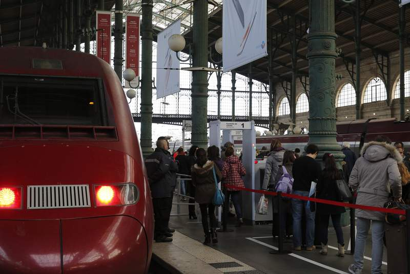 FILE - In this file photo dated Sunday, Dec. 20, 2015, passengers walk through a metal detector at the Grare du Nord train station in Paris, installed in response to a terror attack aboard a train. Islamic State operative Ayoub El Khazzani goes on trial Monday Nov. 16, 2020, in France on terror charges for appearing on a train with an arsenal of weapons and shooting one passenger in 2015. (AP Photo/Christophe Ena, FILE)
