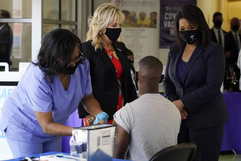 La enfermera Glendora Singleton aplica la inyeccin de una vacuna contra el COVID-19 a Bryan Wilson, estudiante de la universidad Jackson State, el martes 22 de junio de 2021 en Jackson, Mississippi. Los observan la primera dama de Estados Unidos, Jill Biden (atrs, al centro), y Jasmin Chapman, directora del centro de salud de Jackson-Hinds. (AP Foto/Rogelio V. Solis)