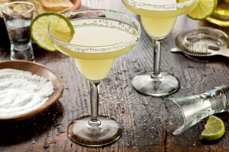 Delicious tequila and lime margaritas on a bar top with tortilla chips and pico de gallo.