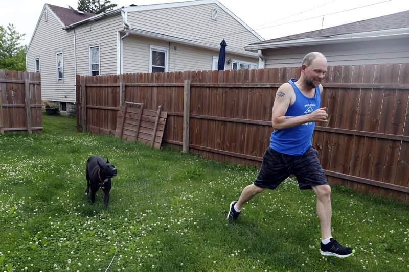 Christian Hainds juega con su perra Reyna en el patio de su casa en Hammond, Indiana, el 7 de junio de 2021. Muchas personas con obesidad en EEUU comenzaron a llevar una vida ms saludable durante la pandemia. (AP Foto/Shafkat Anowar)