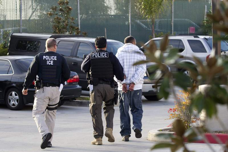 FILE - In this March 30, 2012 file photo, Immigration and Customs Enforcement (ICE) agents take a suspect into custody as part of a nationwide immigration sweep in Chula Vista, Calif. San Diego County Sheriff Bill Gore says he will comply with U.S. Immigration and Customs Enforcement's request for information on four people with criminal records, becoming the first state or local law enforcement official in the country to so honor such requests among a spate of jurisdictions whose laws sharply restrict cooperation with immigration authorities. (AP Photo/Gregory Bull,File)