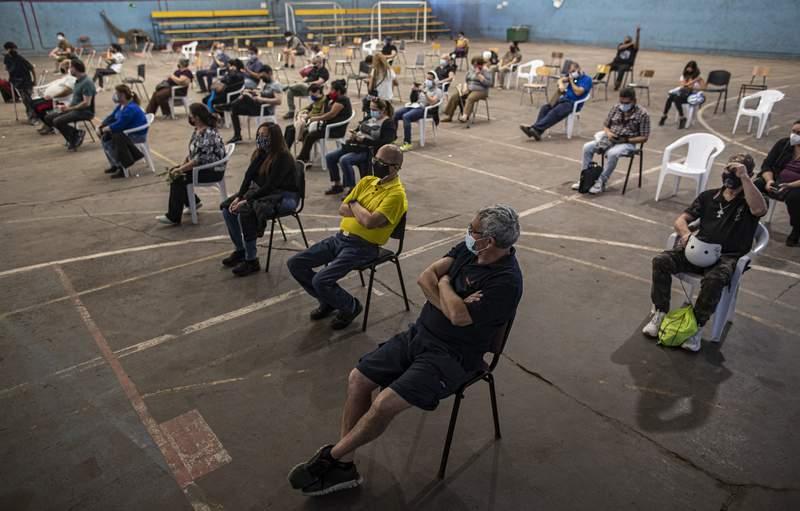 Personas se sientan un rato bajo observacin despus de recibir la vacuna de Pfizer contra el COVID-19 en el polideportivo Jos Manuel Lpez en Santiago, Chile, el mircoles 7 de abril de 2021. Mientras avanza el proceso de inmunizacin, Chile enfrenta cifras rcords en contagios y enfermos en unidades crticas a raz de un fuerte repunte de la pandemia. (AP Foto/Esteban Flix)