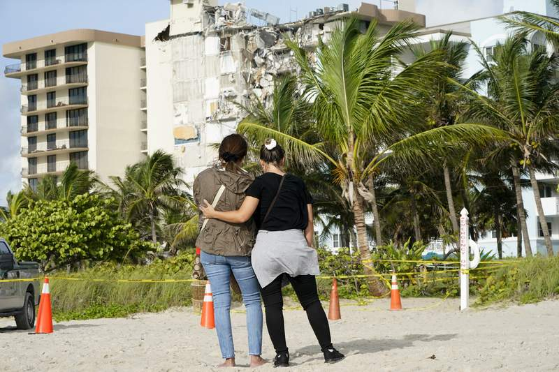 Maria Fernanda Martinez, left, and Mariana Corderiro, right, of Boca Raton, Fla., stand outside of the 12-story beachfront condo building that partially collapsed last week.