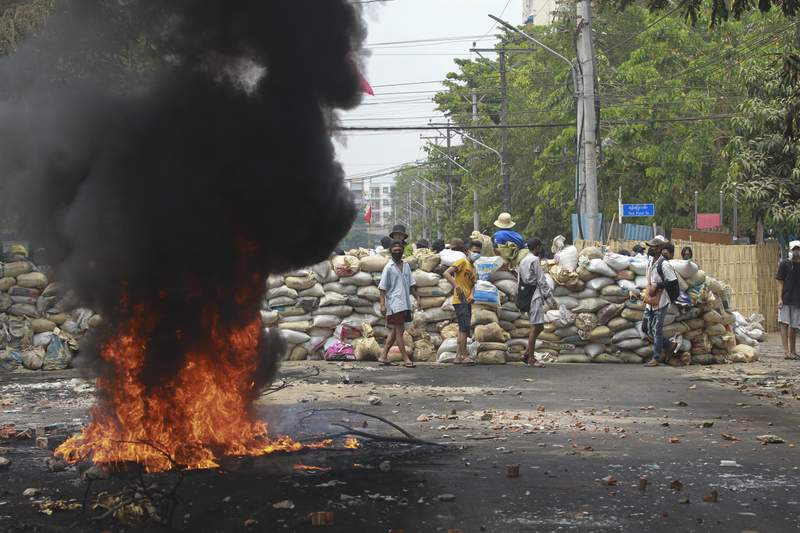 Anti-coup protesters stand beside a burning tire as they fortify their position against the military during a demonstration in Yangon, Myanmar on Tuesday March 30, 2021. Thailands prime minister denied Tuesday that his countrys security forces have sent villagers back to Myanmar who fled from military airstrikes and said his government is ready to shelter anyone who is escaping fighting.(AP Photo)