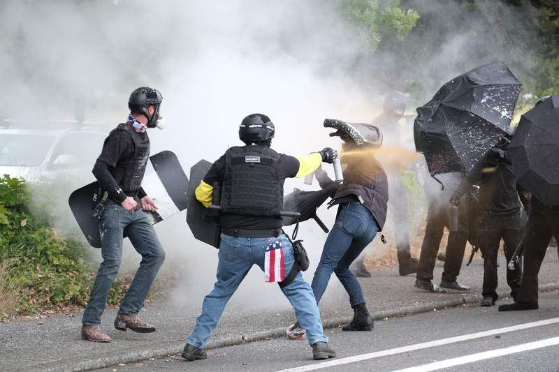 """FILE - In this Sunday, Aug. 22, 2021 file photo, members of the far-right group Proud Boys and anti-fascist protesters spray bear mace at each other during clashes between the politically opposed groups in Portland, Ore. Nearly three weeks after the armed far-right and far-left protesters violently clashed in the streets of a diverse neighborhood Portland's mayor said Wednesday, Sept. 8 a lack of police intervention was """"not the right strategy."""" (AP Photo/Alex Milan Tracy, File)"""