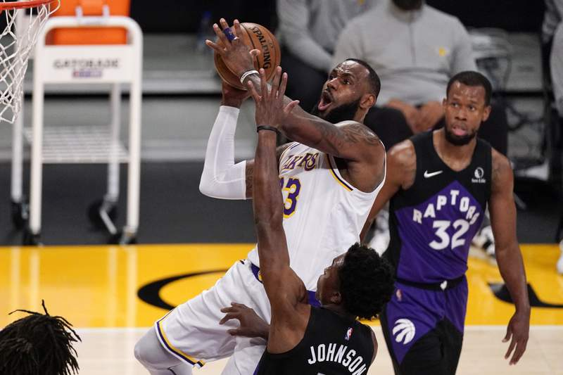Los Angeles Lakers forward LeBron James, upper left, shoots as Toronto Raptors forward Stanley Johnson, lower left, and guard Rodney Hood defend during the first half of an NBA basketball game Sunday, May 2, 2021, in Los Angeles. (AP Photo/Mark J. Terrill)