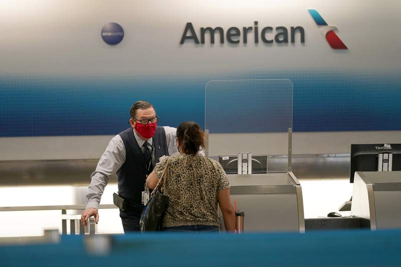 FILE - American Airlines ticket agent Henry Gemdron, left, works with a customer at Miami International Airport during the coronavirus pandemic, Wednesday, Sept. 30, 2020, in Miami.  U.S. airlines began furloughing more than 32,000 employees on Thursday after a federal prohibition on job cuts expired. American Airlines and United Airlines said that they could reverse the furloughs if Congress and the White House quickly agree to provide billions more in taxpayer help to the embattled airline industry.(AP Photo/Lynne Sladky, File)