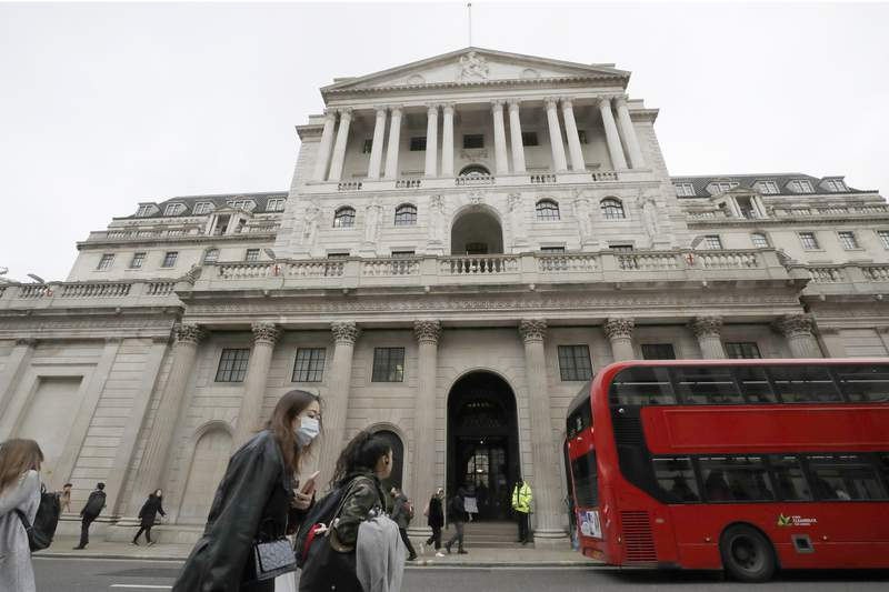 FILE - In this Wednesday, March 11, 2020 file photo, pedestrians wearing face masks pass the Bank of England in London. The Bank of England said Thursday May 6, 2021, it will keep interest rates on hold and has grown more optimistic about the economic recovery in the U.K. as a result of the rapid rollout of coronavirus vaccines. (AP Photo/Matt Dunham, File)