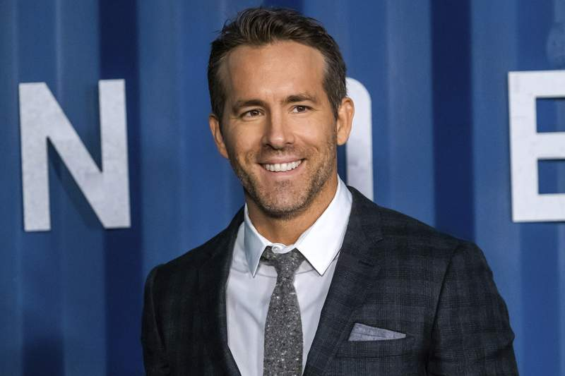"""FILE - In this Tuesday, Dec. 10, 2019 file photo, Ryan Reynolds attends the premiere of Netflix's """"6 Underground"""" at The Shed at Hudson Yards on in New York. Hollywood stars Ryan Reynolds and Rob McElhenney could be getting into the soccer business. Wrexham is a Welsh team which plays in the fifth tier of English soccer. It has revealed on Wednesday, Sept. 23, 2020 that Reynolds and McElhenney are the two extremely well-known individuals the club has previously said are interested in investing 2 million pounds ($2.5 million). (Photo by Charles Sykes/Invision/AP, file)"""