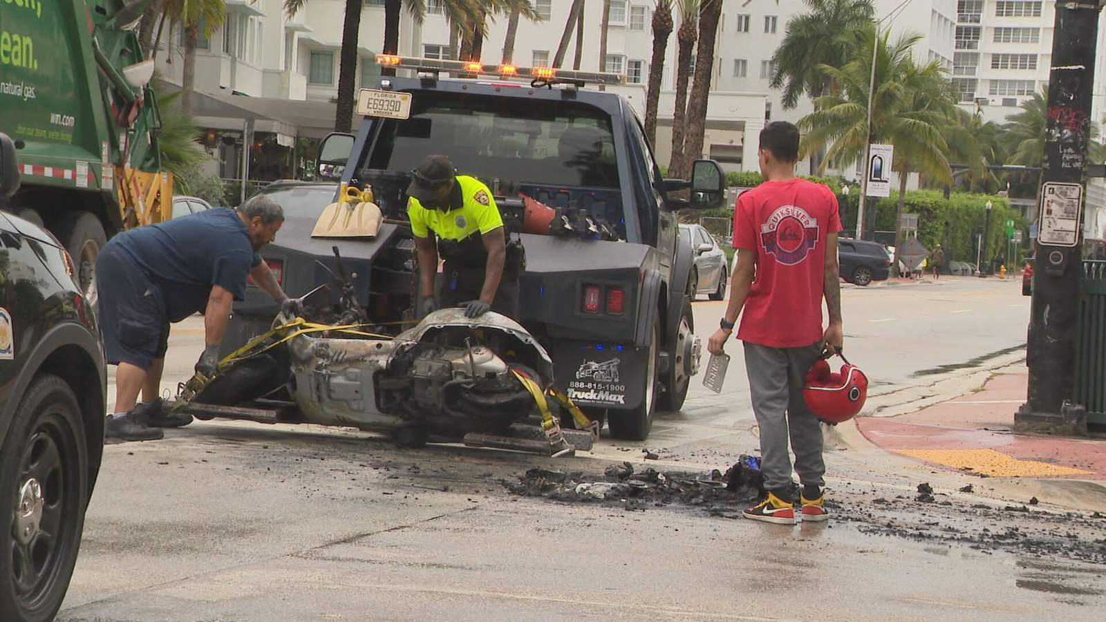 Juan Patano, right, holds on to his helmet as a Miami Beach police officer and a tow truck driver deal with his scooter after a crash on Wednesday in Miami Beach.