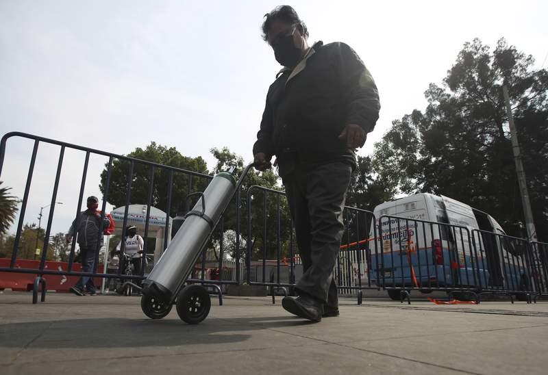 Una persona empuja un tanque de oxgeno para un familiar enfermo de COVID-19 el viernes 15 de enero de 2021, en el distrito de Iztapalapa, en la Ciudad de Mxico. (AP Foto/Marco Ugarte)