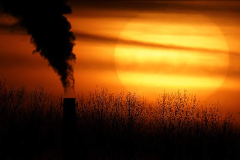 FILE - In this Feb. 1, 2021 file photo, emissions from a coal-fired power plant are silhouetted against the setting sun in Independence, Mo. President Joe Biden is convening a coalition of the willing, the unwilling, the desperate-for-help and the avid-for-money for a two-day summit aimed at rallying the worlds worst polluters to do more to slow climate change. Bidens first task when his virtual summit opens Thursday is to convince the world that the United States is both willing and able isnt just willing to meet an ambitious new emissions-cutting pledge, but also able.  (AP Photo/Charlie Riedel, File)