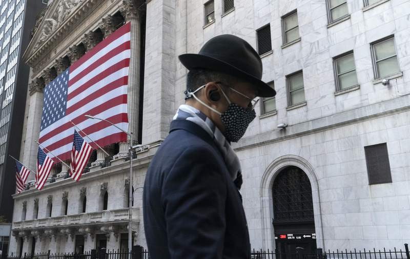 FILE - In this Nov. 16, 2020 file photo a man wearing a mask passes the New York Stock Exchange in New York.  Time stood still for most of the world in 2020, as lockdown life had every day bleeding into the next. But for Wall Street, its been a year locked in at super fast-forward. The stock market tumbled through years worth of losses in just over a month this spring, only to turn around and pack an entire bull markets worth of gains into less than nine months.  (AP Photo/Mark Lennihan, File)