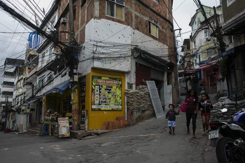 Unos residentes caminan frente a un edificio con orificios de bala das despus de un operativo de la polica en la favela de Jacarezinho, en Ro de Janeiro, Brasil, el sbado 8 de mayo de 2021. (AP Foto/Bruna Prado)