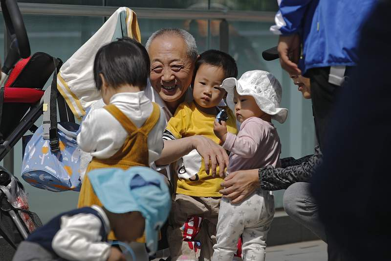 An elderly man plays with children near a commercial office building in Beijing on May 10, 2021. China's ruling Communist Party will ease birth limits to allow all couples to have three children instead of two to cope with the rapid rise in the average age of its population, a state news agency said Monday, May 31. (AP Photo/Andy Wong)