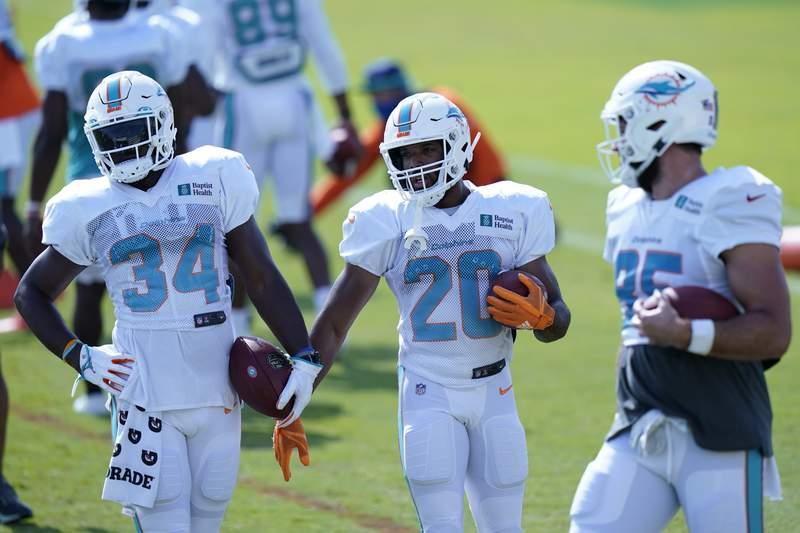Miami Dolphins running backs Jordan Howard (34) and Matt Breida (20) run drills during practice at the NFL football team's training facility, Friday, Aug. 21, 2020, in Davie, Fla. (AP Photo/Lynne Sladky)