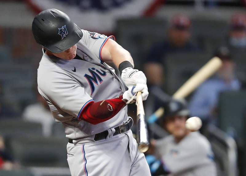 Garrett Cooper of the Miami Marlins hits an RBI single in the tenth inning against the Atlanta Braves at Truist Park on April 12, 2021 in Atlanta, Georgia.