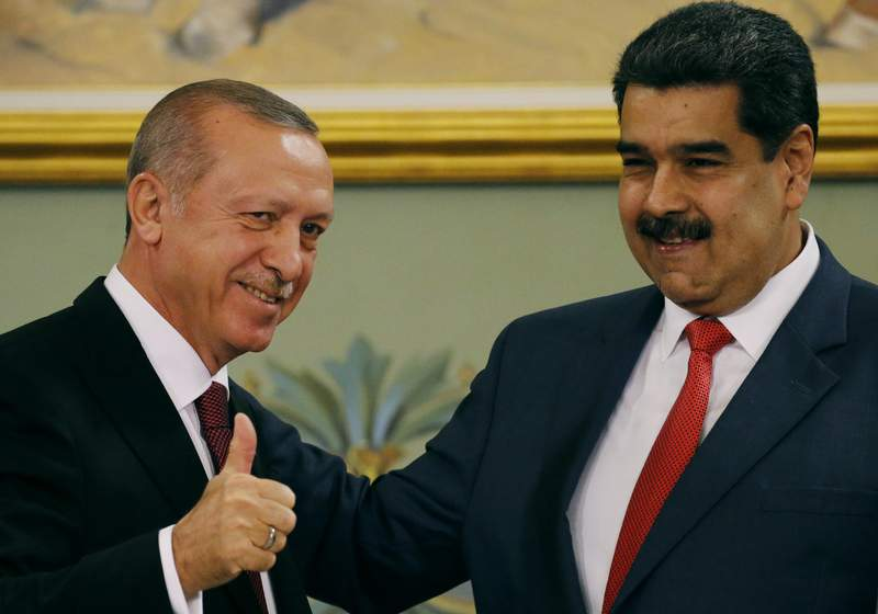 FILE - In this Dec. 3, 2018 file photo, Turkey's President Recep Tayyip Erdogan give a thumbs up as he embraces Venezuela's President Nicolas Maduro during a ceremony at Miraflores presidential palace in Caracas, Venezuela, Monday, Dec. 3, 2018. The personal relationship between the leaders is warm, partly forged by mutual support during domestic attempts to force them from power. (AP Photo/Ariana Cubillos, File)