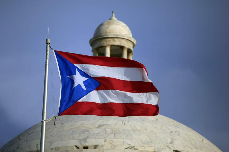 FILE - In this July 29, 2015 file photo, the Puerto Rican flag flies in front of Puerto Rico's Capitol as in San Juan, Puerto Rico. A federal control board that oversees Puerto Ricos finances approved on Wednesday, July 1, 2020, a new budget that largely suspends austerity measures and government cuts for one year as the U.S. territory struggles to recover from hurricanes, earthquakes and the pandemic. (AP Photo/Ricardo Arduengo, File)