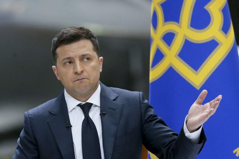 Ukrainian President Volodymyr Zelenskyy gestures while speaking to the media during a news conference with the world's largest airplane, Ukrainian Antonov An-225 Mriya in the background, at the Antonov aircraft factory in Kyiv, Ukraine, Thursday, May 20, 2021. (AP Photo/Efrem Lukatsky)