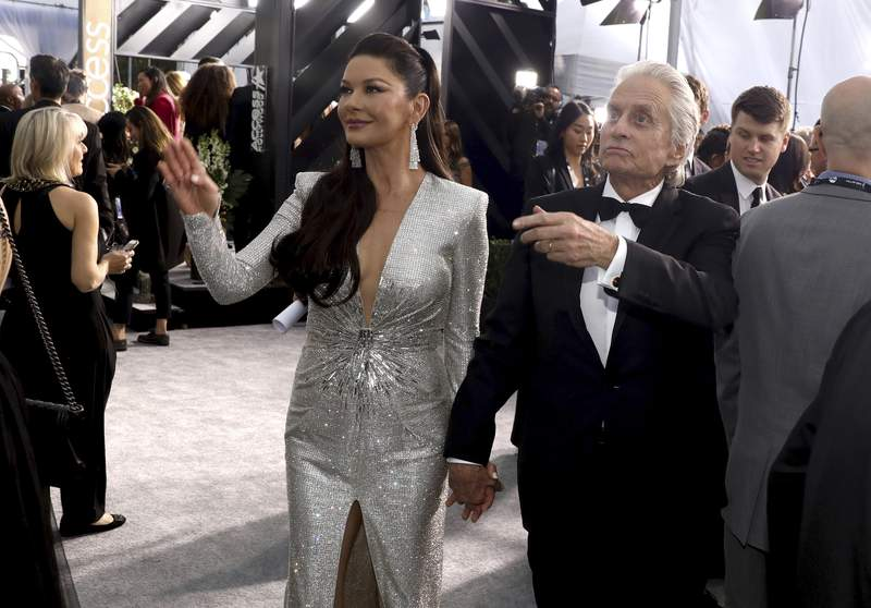 FILE - In this Jan. 19, 2020 file photo, Catherine Zeta-Jones and Michael Douglas arrive at the 26th annual Screen Actors Guild Awards, in Los Angeles, California. Hollywood power couple Michael Douglas and Catherine Zeta-Jones are set to return to Israel as co-hosts of this years prestigious Genesis Prize ceremony. The Genesis Prize Foundation announced Wednesday, Feb 25, 2020, that the pair would co-host the June 18 event, where former Soviet dissident and Israeli politician Natan Sharansky is to be honored as the 2020 laureate. Douglas himself was the 2015 winner of the $1 million prize, granted each year in recognition of professional achievement, contribution to humanity and commitment to Jewish values and Israel. (Photo by Matt Sayles/Invision/AP, File)