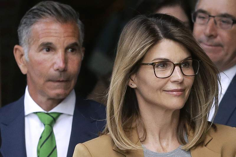FILE - In this April 3, 2019 file photo, actor Lori Loughlin, front, and husband, clothing designer Mossimo Giannulli, left, depart federal court in Boston after facing charges in a nationwide college admissions bribery scandal. Loughlin was released from federal prison in Dublin, Calif., Monday, Dec. 28, 2020, after spending two months behind bars for paying half a million dollars in bribes to get her two daughters into college.   (AP Photo/Steven Senne, File)