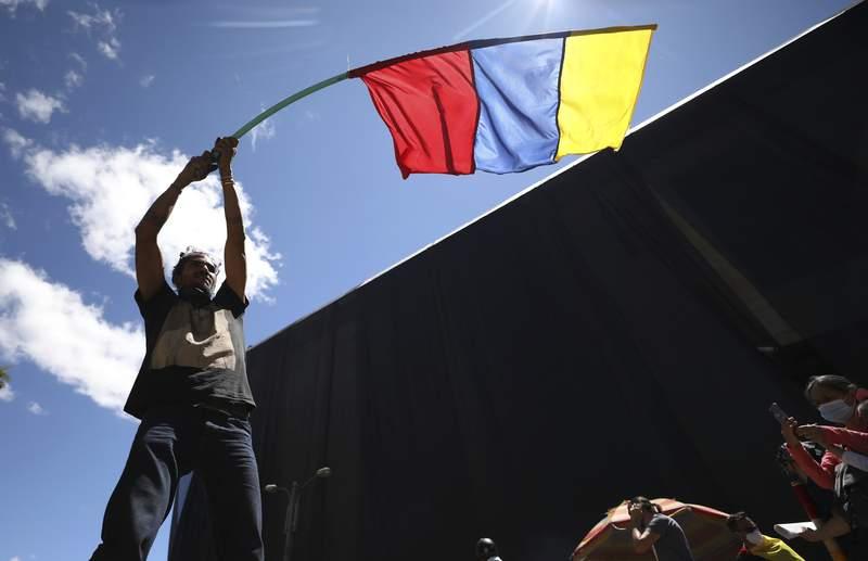 Un hombre ondea una bandera de Colombia el mircoles 2 de junio de 2021 durante una manifestacin antigubernamental, la cual fue desatada por una propuesta de incremento fiscal a los servicios pblicos, el combustible, los salarios y las pensiones, en Bogot, Colombia. (AP Foto/Fernando Vergara)