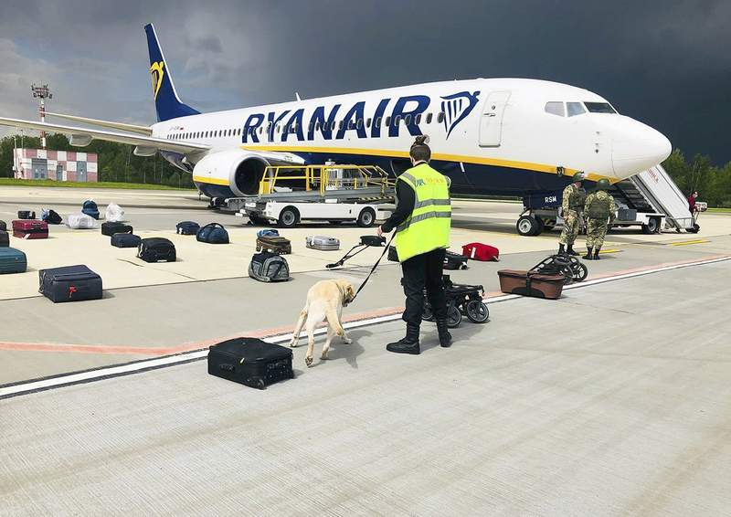 FILE - In this May 23, 2021, file photo provided by ONLINER.BY, security use a dog to check the luggage of passengers on the Ryanair jet that carried opposition figure Raman Pratasevich, traveling from Athens to Vilnius, Lithuania.  Dissident journalist Raman Pratasevich, arrested when Belarus diverted his flight said in a video from prison released Wednesday June 3, 2021, asserted that he has been set up by an unidentified associate. No bomb was found after the landing, but Pratasevich was arrested along with his Russian girlfriend. (ONLINER.BY via AP)