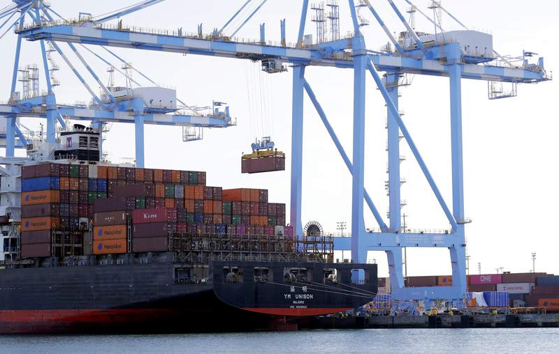 FILE - In this Nov. 4, 2019, file photo cargo cranes are used to take containers off of a Yang Ming Marine Transport Corporation boat at the Port of Tacoma in Tacoma, Wash.  The U.S. trade deficit surged in July 2020 to $63.6 billion, the highest level in 12 years, as imports jumped by a record amount. The Commerce Department reported, Thursday, Sept. 3 2020,  that the July deficit, the gap between what America buys and what it sells to foreigners, was 18.9% higher than the June deficit of $53.5 billion. (AP Photo/Ted S. Warren, File)