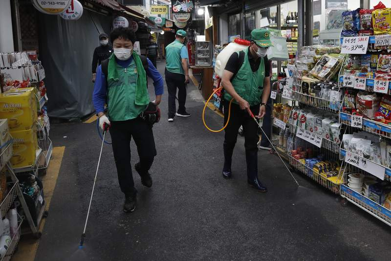 People disinfect as a precaution against the coronavirus at a local market in Seoul, South Korea, Wednesday, Sept. 2, 2020. (AP Photo/Lee Jin-man)