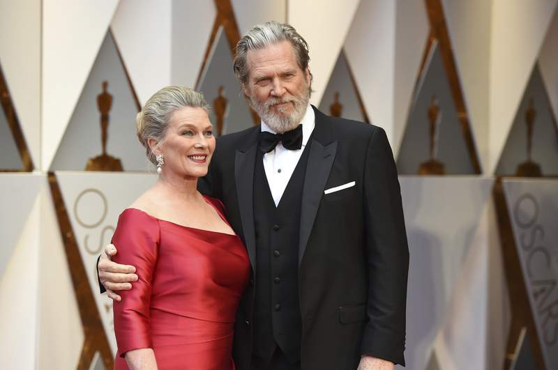 Susan Geston, left, and Jeff Bridges arrive at the Oscars on Sunday, Feb. 26, 2017, at the Dolby Theatre in Los Angeles. Bridges announced on his website Monday, Sept. 13, 2021 that his cancer was in remission and that he and his wife Susan Geston also recovered from COVID-19. (Photo by Jordan Strauss/Invision/AP)