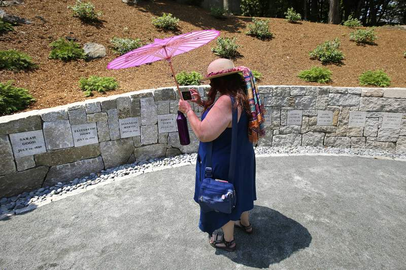FILE - In this July 19, 2017, file photograph, Karla Hailer, a fifth-grade teacher from Scituate, Mass., shoots a video where a memorial stands at the site in Salem, Mass., where five women were hanged as witches more than 325 years earlier. A woman convicted of witchcraft in 1693 and sentenced to death at the height of the Salem Witch Trials finally will be exonerated if Massachusetts lawmakers approve a bill inspired by a curious eighth-grade history class. State Sen. Diana DiZoglio, a Democrat from Methuen, has introduced legislation to clear the name of Elizabeth Johnson Jr., 328 years after she was condemned but never executed. DiZoglio says she was inspired by sleuthing done by a group of 13- and 14-year-olds at North Andover Middle School. (AP Photo/Stephan Savoia, File)