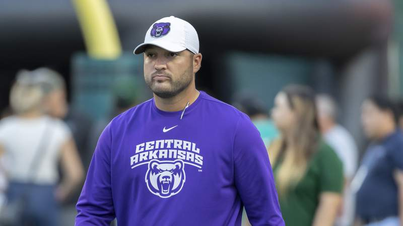 """FILE - In this Sept. 21, 2019, file photo, Central Arkansas head coach Nathan Brown walks on to the field before the start of an NCAA college football game against Hawaii in Honolulu. When Central Arkansas and Austin Peay signed up to play in the first game of the college football season, little did they know how notable it would become. The FCS schools will kick off the shortened season Saturday, Aug. 29, 2020, in the Guardian Classic before a limited number of fans amid the COVID-19 pandemic. Brown says we are the show in Week Zero and the game to really kick off football, not just college football but also professional football."""" (AP Photo/Eugene Tanner, File)"""