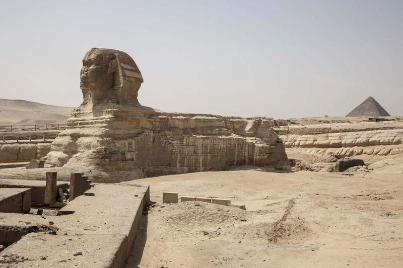 """This March 25, 2020 photo, shows the empty Sphinx complex of the Giza Pyramids in Egypt. """"Everything collapsed in a flash,"""" said Sayed el-Gabri, a souvenir vendor, as he stared at the almost empty complex of Egypt's famed Giza Pyramids. It was not unexpected, but the evaporation of the stream of visitors to the ancient site was still a shock to el-Gabri and other tourism workers. He saw it coming, as the government stepped up its measures to slow the new coronavirus' spread, culminating in a ban on all international flights in and out of the country. (AP Photo/Nariman El-Mofty)"""