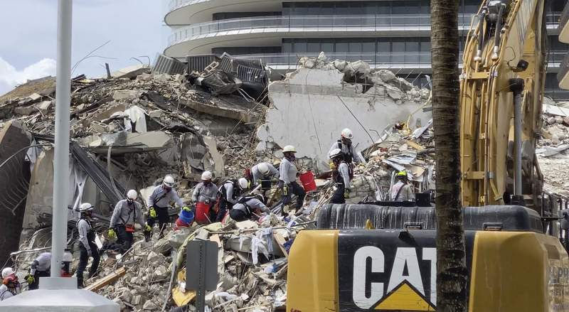 This photo provided by Miami-Dade Fire Rescue, search and rescue personnel search for survivors through the rubble at the Champlain Towers South Condo in Surfside, Fla., section of Miami,  Friday, June 25, 2021. The apartment building partially collapsed on Thursday. (Miami-Dade Fire Rescue via AP)
