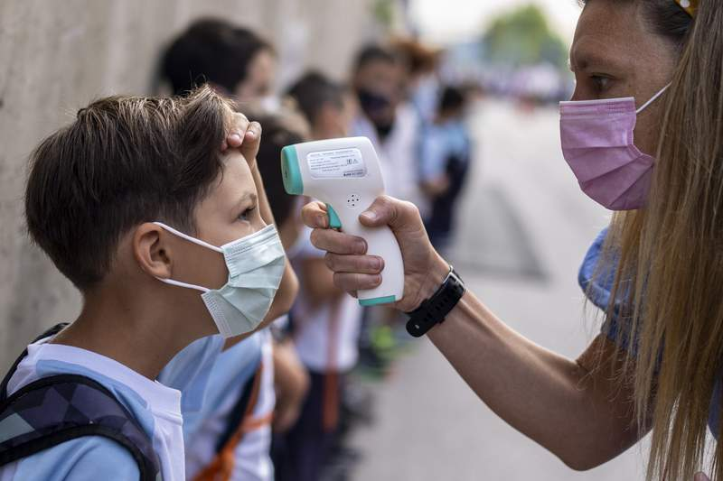 A teacher wearing a face mask to protect against the spread of coronavirus checks the temperature of her pupil at Maestro Padilla school as the new school year begins, in Madrid, Spain, Tuesday, Sept. 7, 2021. Around 8 million children in Spain are set to start the new school year. (AP Photo/Manu Fernandez)