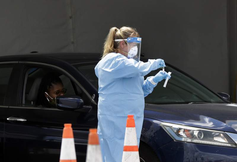 A healthcare worker puts a test swab into a vial after testing a passenger at a drive-through coronavirus testing site outside of Hard Rock Stadium, Friday, June 26, 2020, in Miami Gardens, Fla. Florida banned alcohol consumption at its bars Friday as its daily confirmed coronavirus cases neared 9,000, a new record that is almost double the previous mark set just two days ago. (AP Photo/Wilfredo Lee)