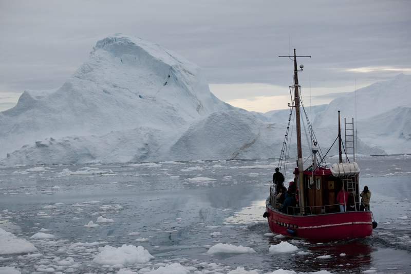 FILE - In this July 18, 2011 file photo, a boat steers slowly through floating ice, and around icebergs, all shed from the Greenland ice sheet, outside Ilulissat, Greenland. Climate historians hunting for past temperature extremes have unearthed what the U.N. weather agency calls a new record low in the Northern Hemisphere. The World Meteorological Organizations publicly confirmed Wednesday Sept. 23, 2020, the all-time cold reading for the hemisphere: -69.6 Celsius recorded on Dec. 22, 1991 at an automatic weather station in a remote site called Klinck, not far from the highest point on the Greenland Ice Sheet. (AP Photo/Brennan Linsley, File)